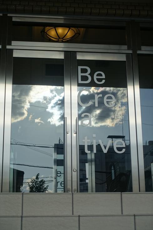会場の玄関に映った雲(4・29)と「Be Creative」の文字